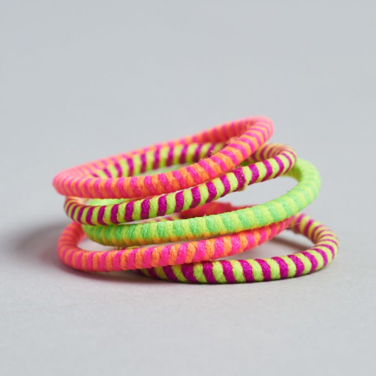 a stack of five small neon hair ties in pink and green