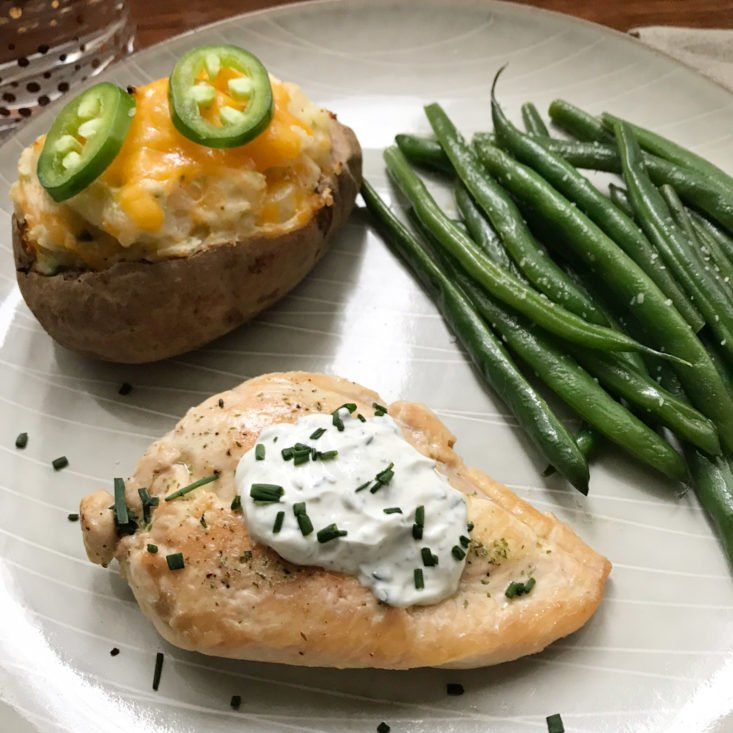 close up of plated ranch chicken with jalapeno popper twice baked potato