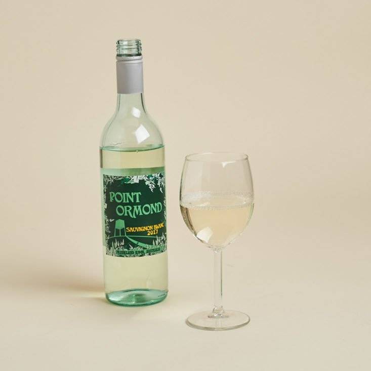 white wine poured in a glass with a bottle next to it