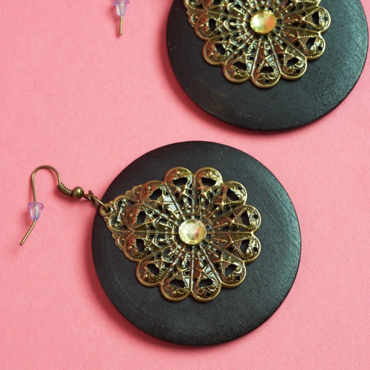These earrings have a dangling stone-like disc and a smaller brass accent.