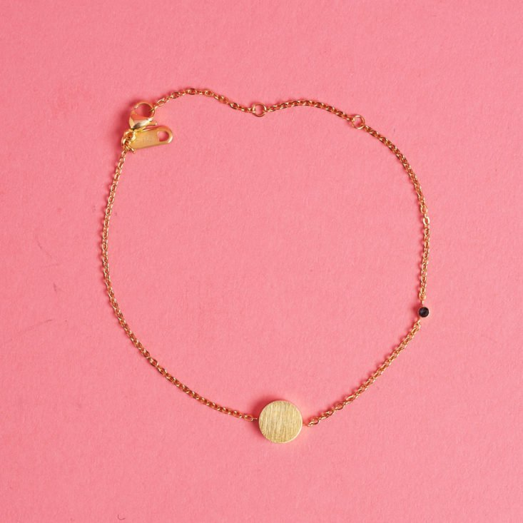 This bracelet features a simple gold charm and a tiny gem