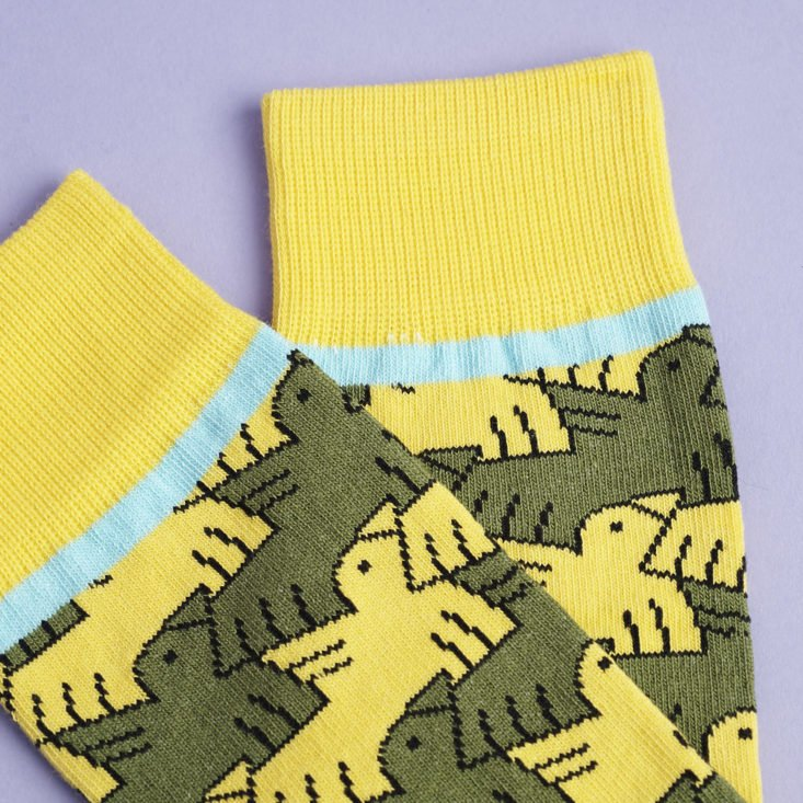 close up of socks with yellow and green bird pattern and aqua blue stripe