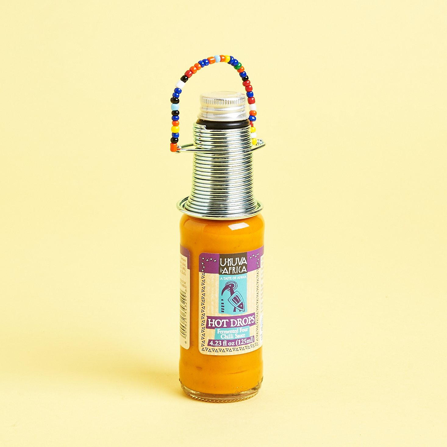hot sauce with decorative neck coiling and multicolored beads